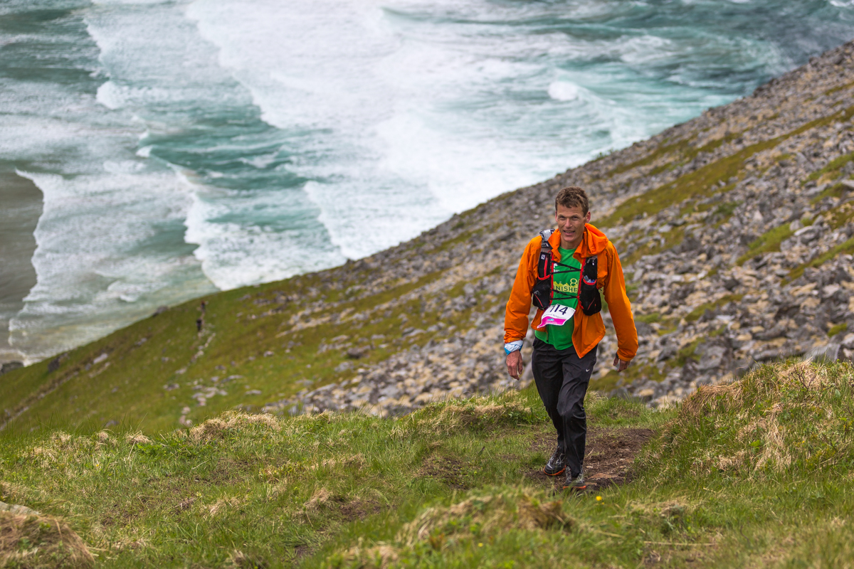 Hallvard Schjølberg, winner of the 100 miles Lofoten Ultra Trail Race climbs above Kvalvika.