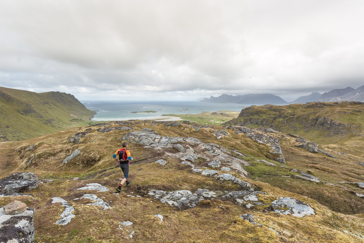 A runner in the 100 miles race of the Lofoten Ultra Trail 2016 quickly negotiates a flatter part of the trail just before the descent to Fredvang.