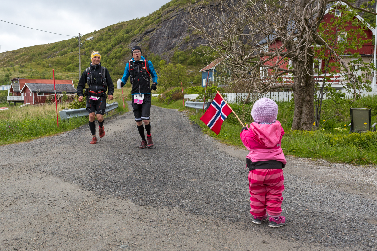 A young child welcomes two runners in the hamlet of Nesland, during the Lofoten Ultra Trail 2016.