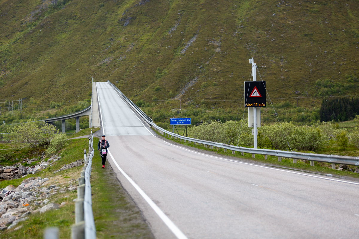 Maria Nordfjell exits Gimsøystraumen Bridge, on 12 m/s wind, during the 100 miles race of the Lofoten Ultra Trail 2016.